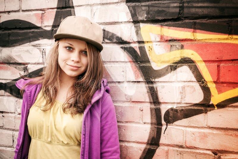 白肤金发的时髦的十几岁的女孩在都市wal附近站立 免版税库存照片