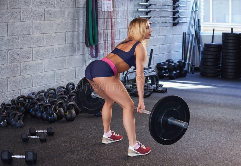 白肤金发的有强健的身体的健身运动的妇女在做与杠铃的运动服deadlift在健身房 库存图片
