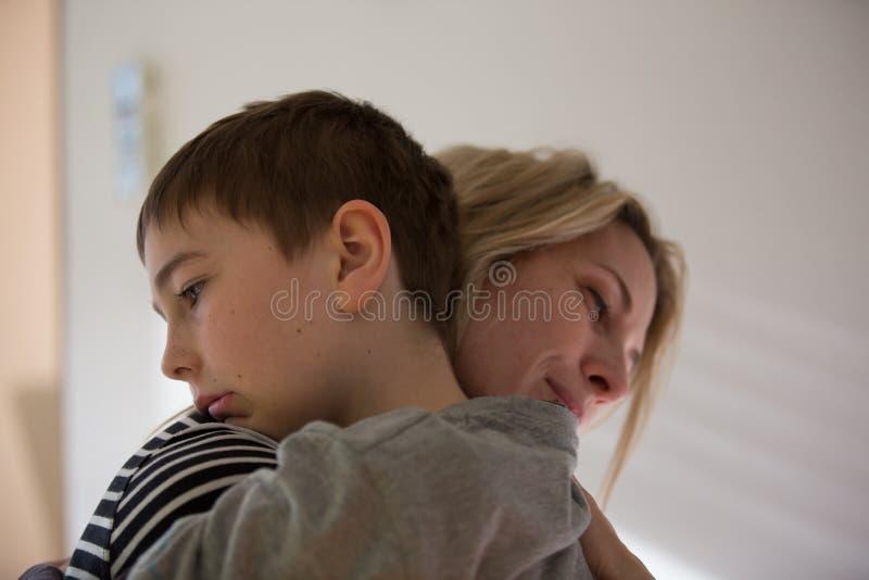 白肤金发的母亲和深色的男孩互相拥抱温暖 室内,自然光 免版税图库摄影