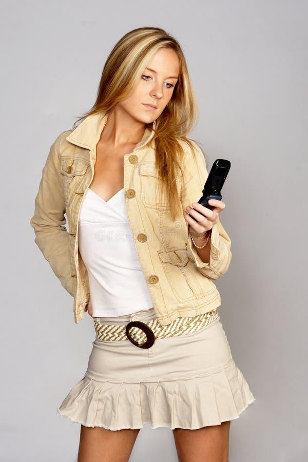 白肤金发的熟悉内情的移动电话妇女&# 免版税库存图片