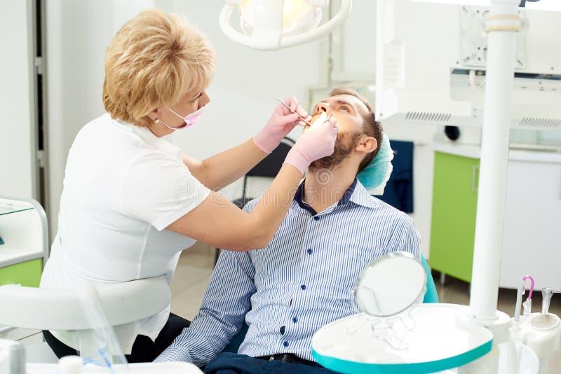 白肤金发的牙医专家给牙齿治疗一个现代牙齿诊所的一个男性客户 库存照片