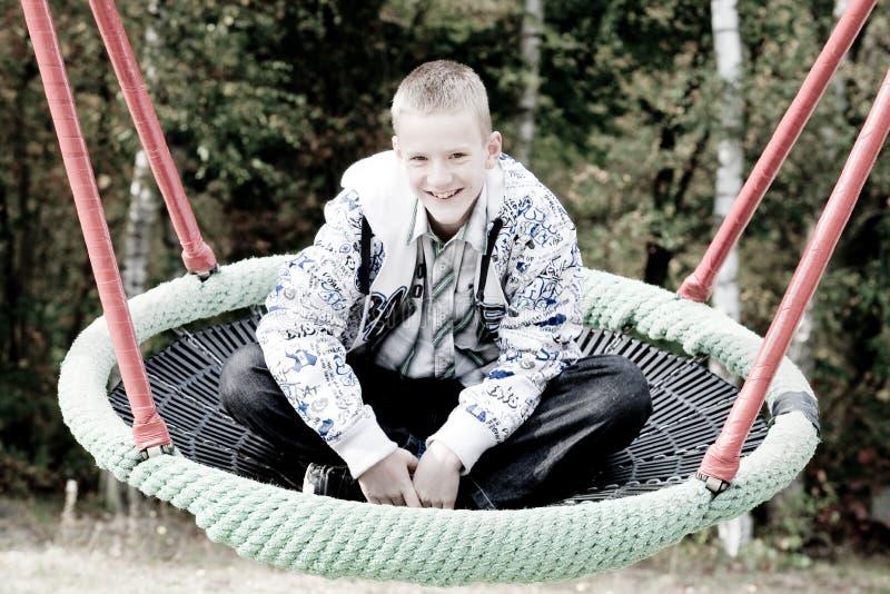 白肤金发的男孩愉快的摇摆 免版税图库摄影