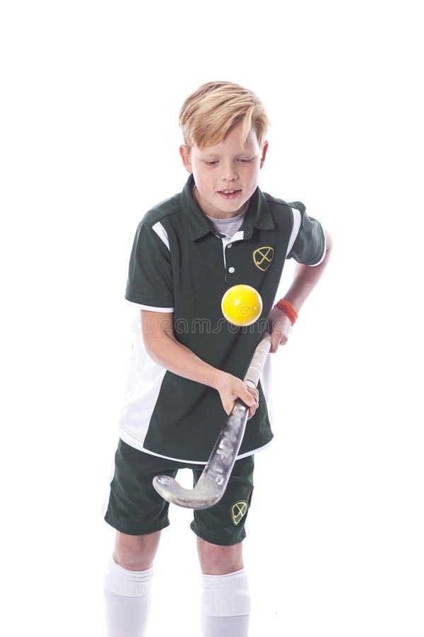 年轻白肤金发的男孩用曲棍球棍子 库存图片