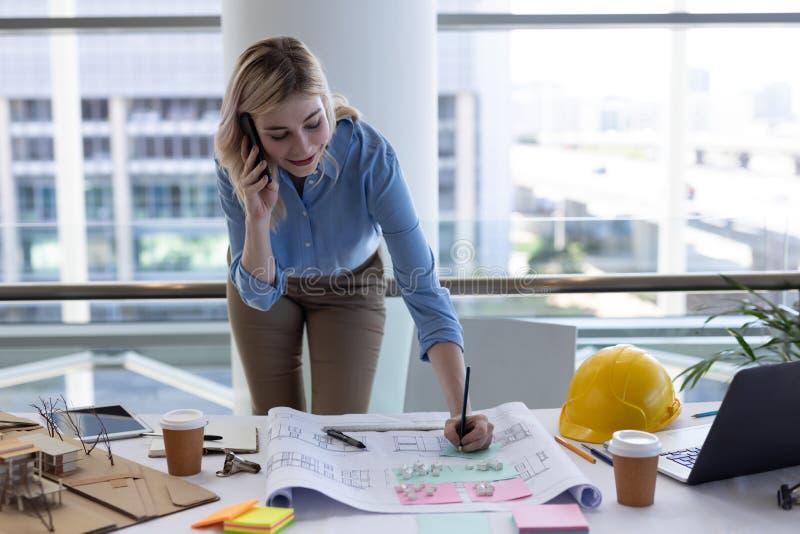 白肤金发的白种人女性建筑师谈话在手机,当工作在书桌在办公室时 库存图片