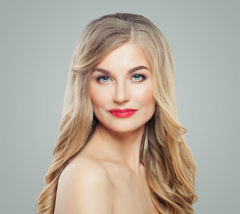 白肤金发的秀丽 有长的健康卷发、清楚的皮肤和红色嘴唇构成的完善的妇女 面部治疗 免版税库存图片
