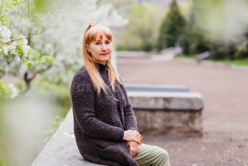 白肤金发的美丽的中年妇女在公园坐开花苹果树背景  免版税库存图片
