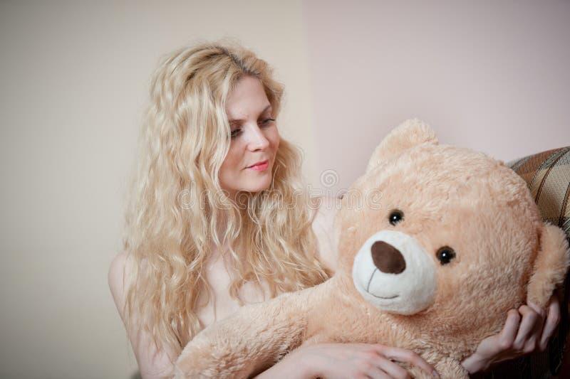 年轻白肤金发的肉欲的妇女坐放松与一个巨大的玩具熊的沙发 免版税库存照片