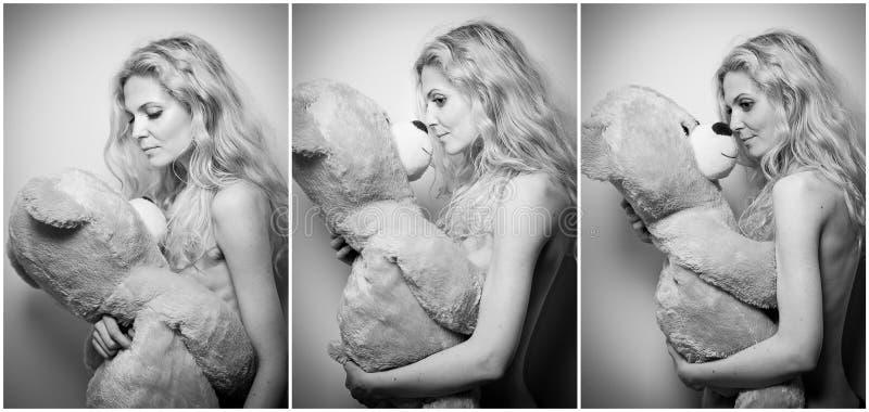 年轻白肤金发的肉欲的妇女坐放松与一个巨大的玩具熊的沙发 库存照片