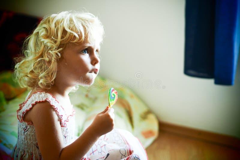 白肤金发的蓝眼睛的女婴用一个糖果在她的手上 免版税库存照片