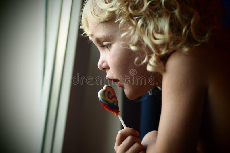 白肤金发的蓝眼睛的女婴用一个糖果在她的看窗口的手上 库存照片