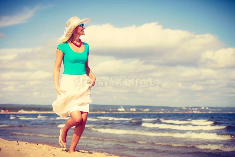 白肤金发的走在海滩的妇女佩带的礼服 免版税库存图片