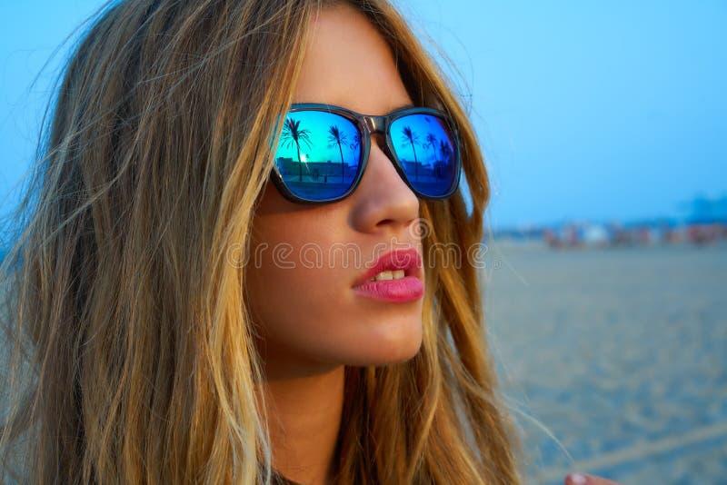 白肤金发的青少年的女孩太阳镜棕榈树日落 免版税库存图片