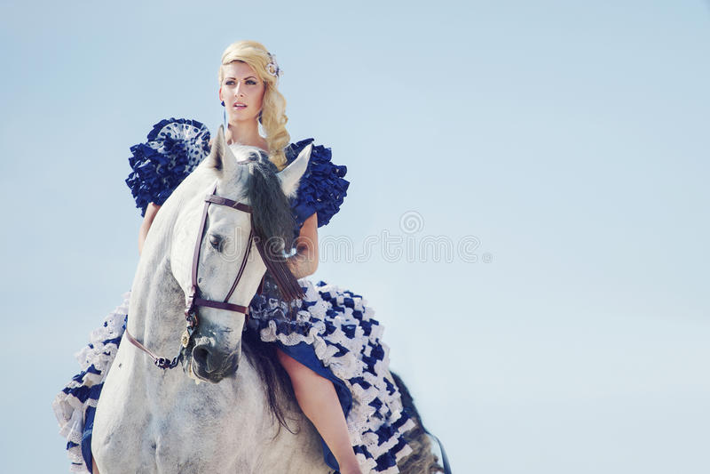 白肤金发的骑马的画象马 免版税库存图片