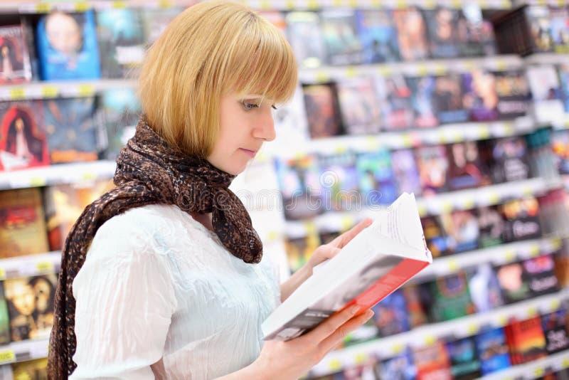 白肤金发的girlreads书在超级市场 库存图片