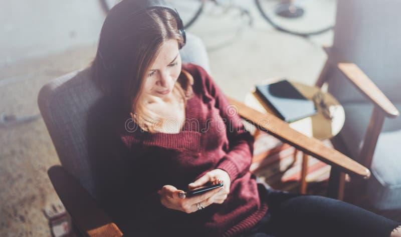 白肤金发的yound妇女在手上的拿着现代手机 指向在空的接触流动屏幕上的女孩手指晴朗 免版税库存照片