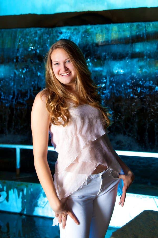 白肤金发青少年在蓝色瀑布前面 免版税图库摄影