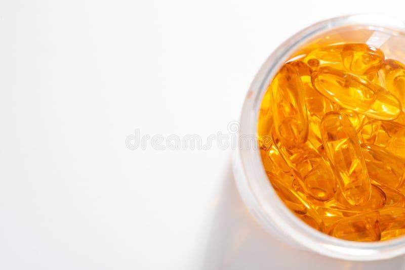 白背景黄胶囊瓶的特写 库存图片