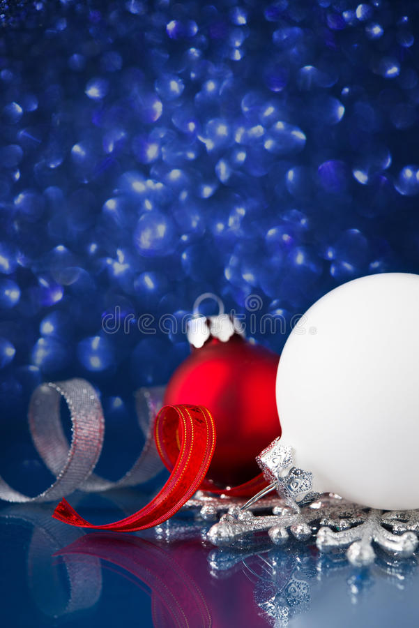 白色、银和红色圣诞节装饰品在深蓝bokeh背景与空间文本的 免版税图库摄影