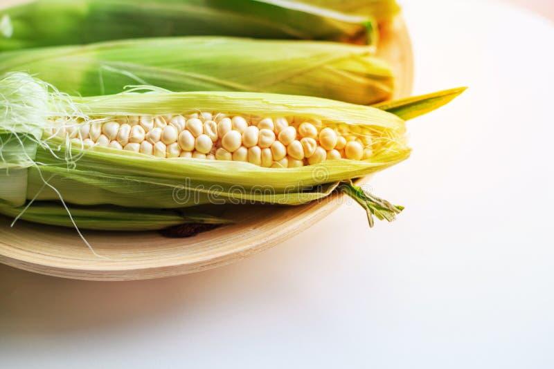 白色乳状甜玉米的新鲜的耳朵与绿色叶子的在木盘子有白色桌背景 有机蔬菜,素食主义者农场 免版税图库摄影