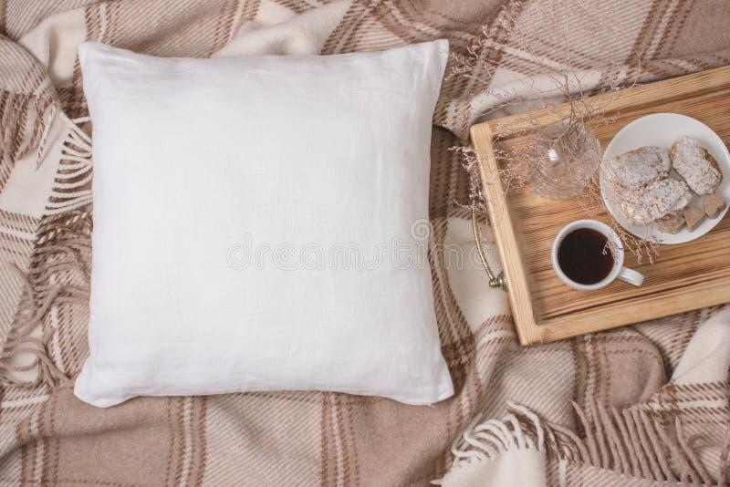 白色亚麻制枕头,在格子花呢披肩的坐垫大模型 Inrerior照片 库存照片