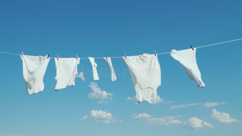 白色亚麻布在绳索烘干反对天空蔚蓝 图库摄影