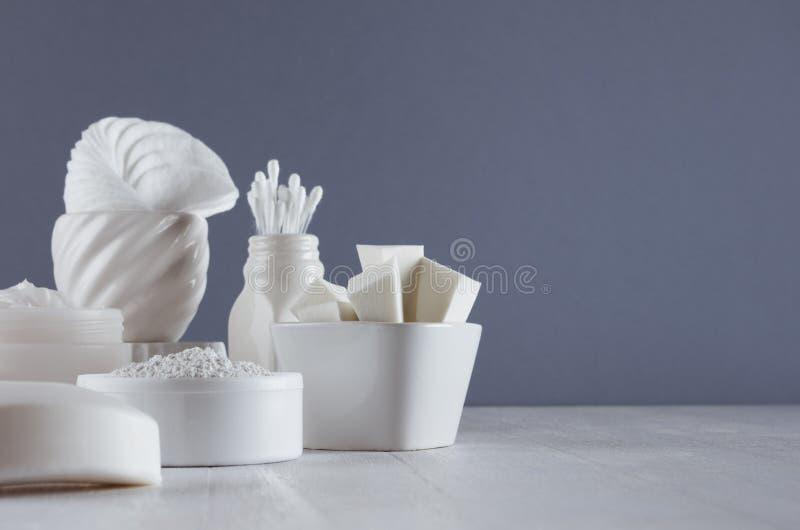 白色产品化妆用品大模型面孔护肤的在典雅的现代灰色黑暗的卫生间内部 免版税库存图片