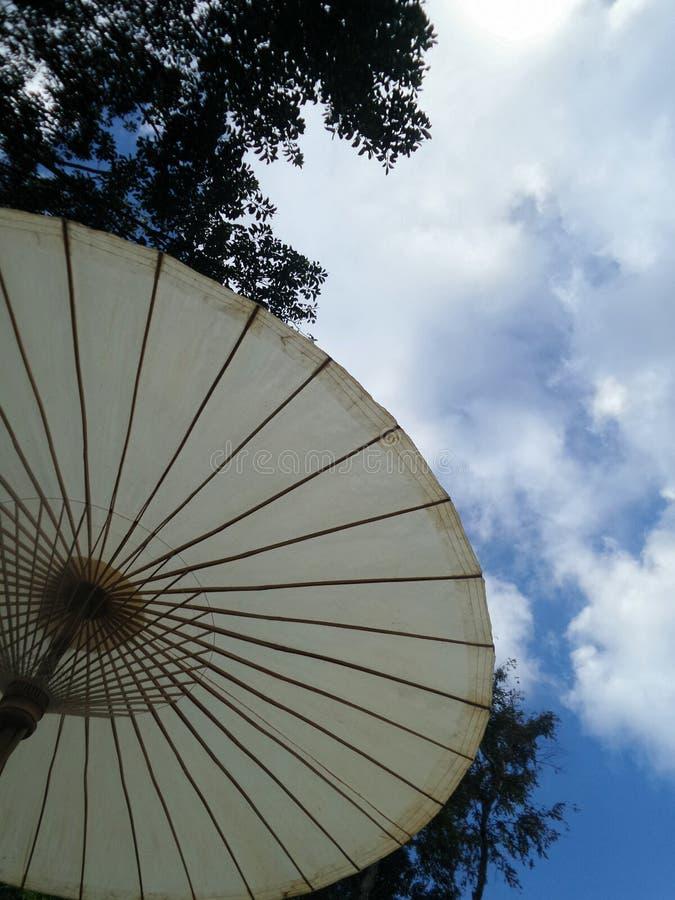 白色伞在蓝天下 库存图片