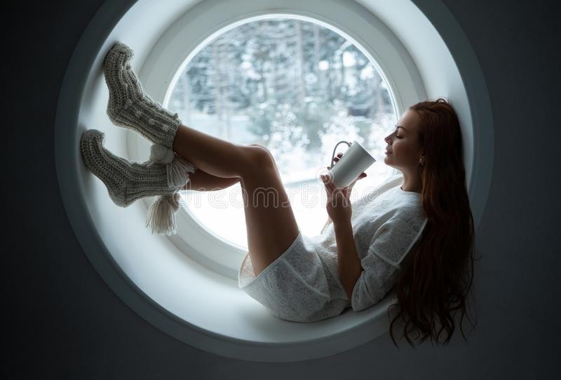 白色体育穿戴alies的女孩在窗口 图库摄影