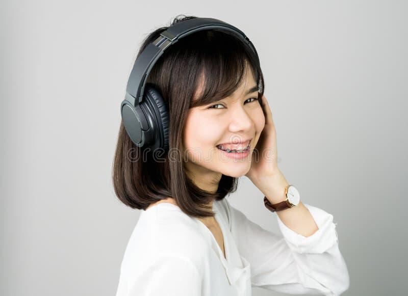 白色便服的亚裔女孩听到从黑耳机的音乐的 库存照片