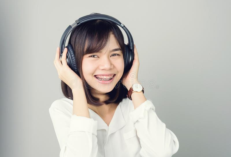 白色便服的亚裔女孩听到从黑耳机的音乐的 库存图片
