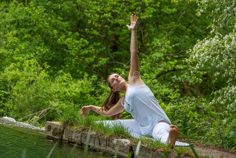 白色做的瑜伽的女孩 库存图片
