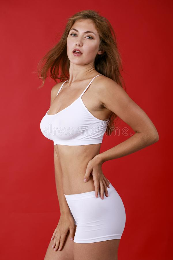 白色健身衣物的年轻美丽的白肤金发的妇女 库存图片