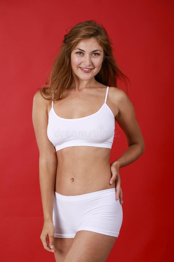 白色健身衣物的年轻美丽的白肤金发的妇女 免版税图库摄影