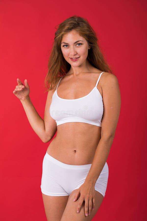 白色健身衣物的年轻美丽的白肤金发的妇女 免版税库存图片