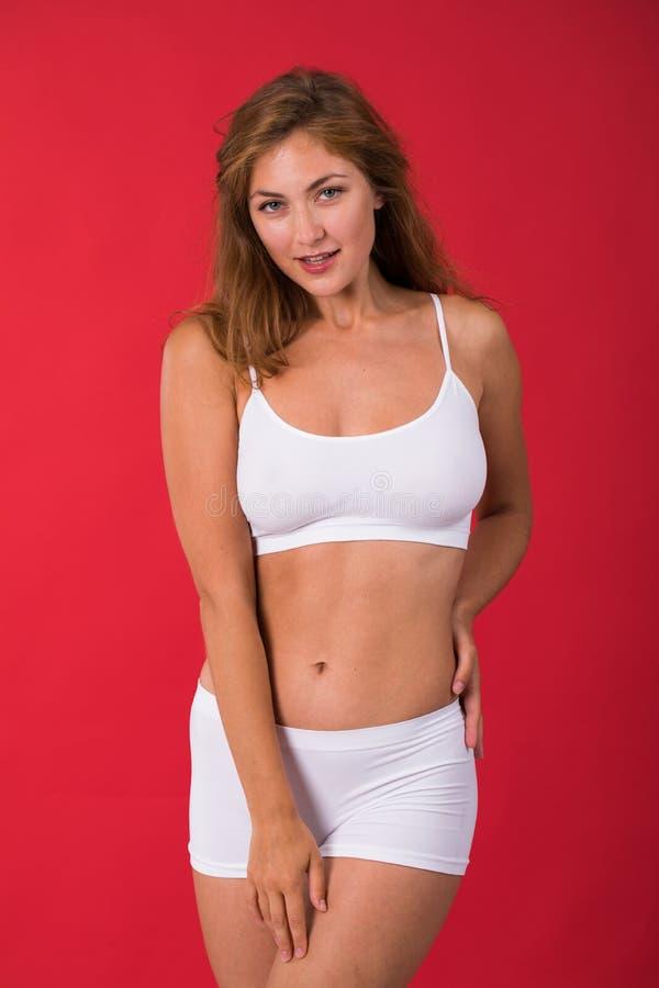 白色健身衣物的年轻美丽的白肤金发的妇女 库存照片