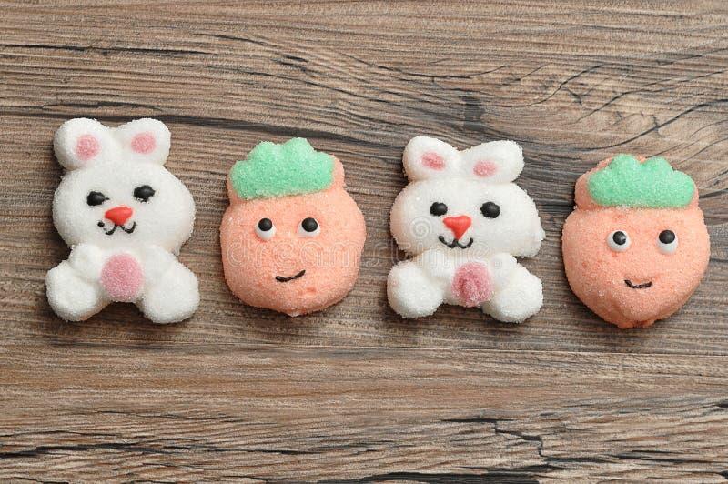 白色兔宝宝形状蛋白软糖行和桃子塑造蛋白软糖 免版税库存照片
