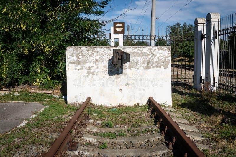 白色具体缓冲桩站立在铁路轨道结束时的,局限制约界限 库存照片