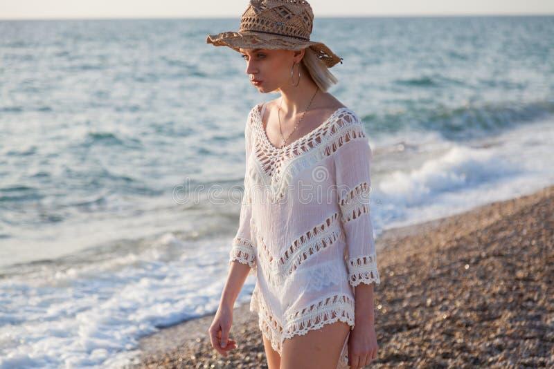 白色内衣和一个帽子的美丽的时髦的女人在海滩海洋 库存照片