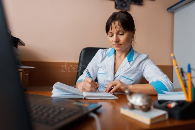 白色制服的一位女性医生在笔记本坐在一张木桌上在她的办公室并且写着某事 工作日 库存照片