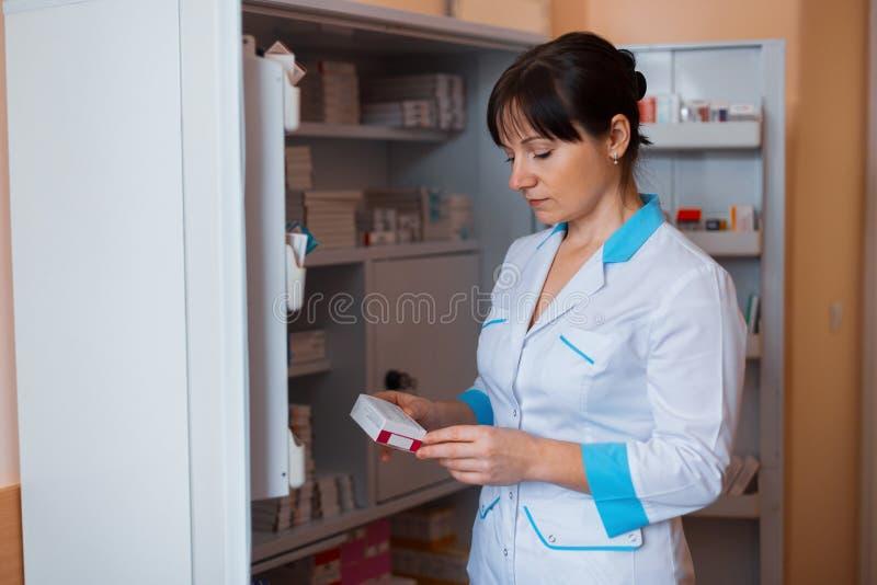 白色制服的一位年轻女性医生在医护人员的一间屋子里站立在有药片的一个内阁附近 免版税图库摄影