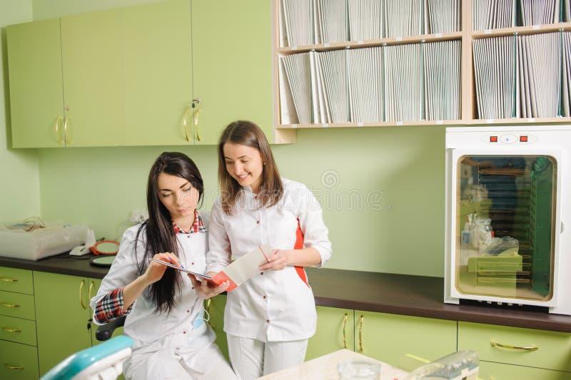 白色制服的两位女性医生在诊所办公室 牙科 库存图片