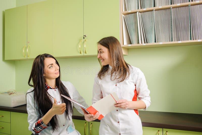 白色制服的两位女性医生在诊所办公室 牙科 免版税库存图片
