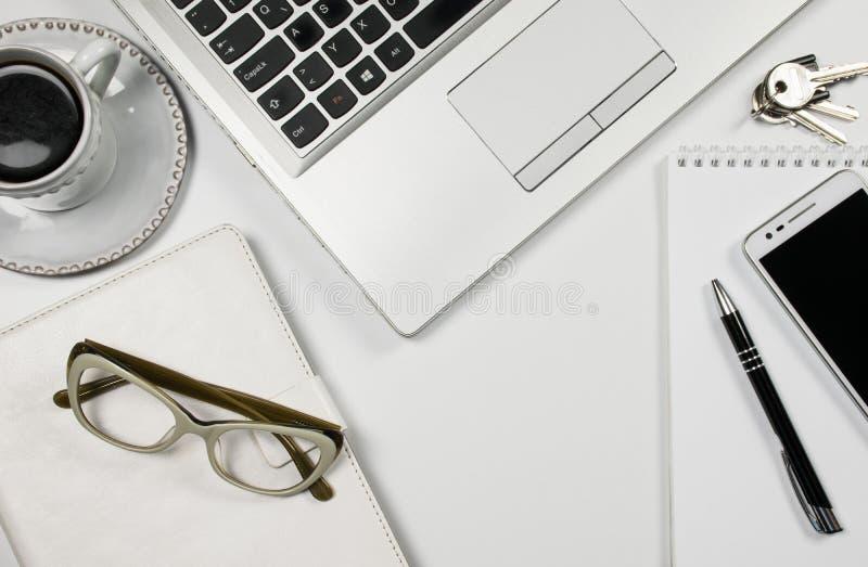 白色办公桌台式视图、膝上型计算机、咖啡,手机、玻璃、铅笔笔记薄和白色背景 库存图片