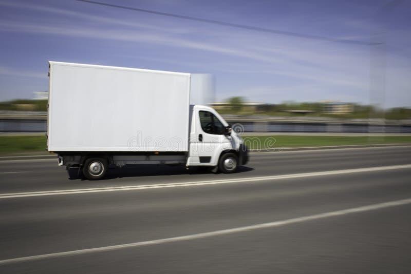 白色加速在街道上的送货车 图库摄影