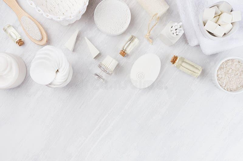 白色化妆用品设置了身体关心和浴辅助部件的自然产品作为在白色木板,顶视图的边界 免版税库存照片