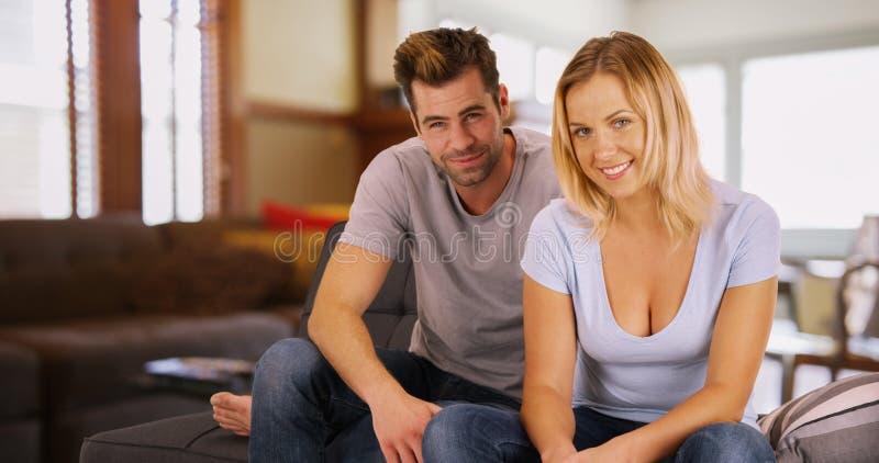 白色千福年的夫妇画象坐微笑对照相机的长沙发 库存照片