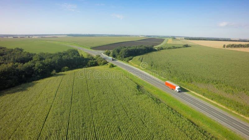 白色卡车空中顶视图有继续前进在方向的半货物拖车的路 库存照片