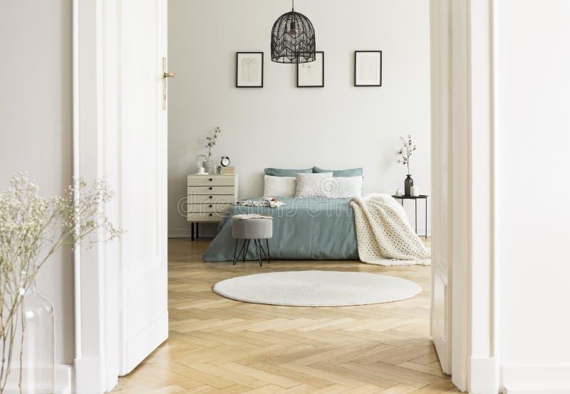 白色卧室内部真正的照片与圆的地毯,特大b的 免版税库存图片
