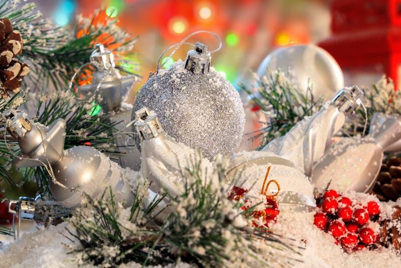 白色发光的球和圣诞节玩具在积雪的杉木分支说谎以红色灯笼和色的光为背景 免版税库存照片