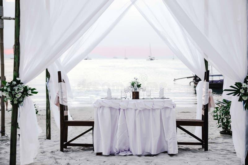白色口气 在热带海滩的浪漫豪华晚餐在日落 与藤的装饰的桌在它和椅子 免版税库存图片